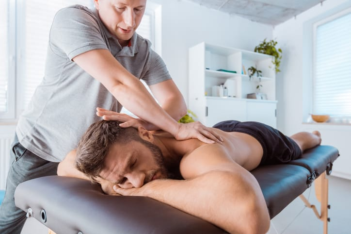 Starting your own massage therapy practice, therapist massages back of man in private practice massage room