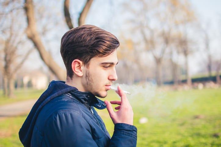 Teenage boy smoking a cigarette at risk for poor adolescent dental hygiene