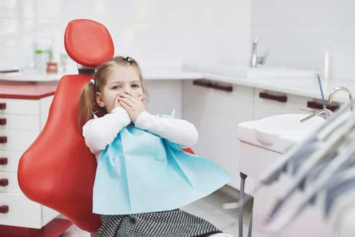 Frightened little girl experiences dental anxiety at dentist office, covers mouth with hands