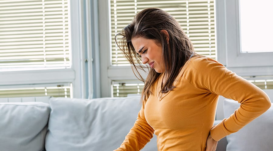 Young woman suffering from chronic pain winces, placing hand over painful spot on back