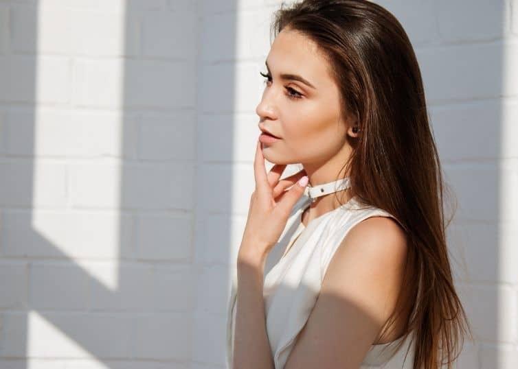 Female model posing against white wall background