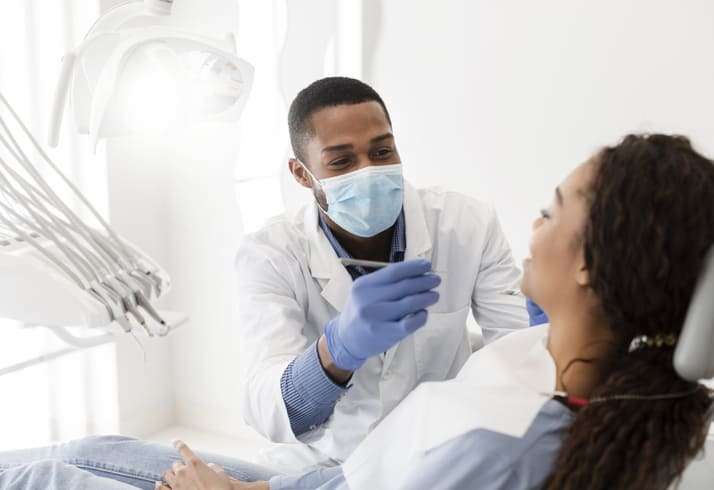 Young African American dentist treating patient in modern clinic