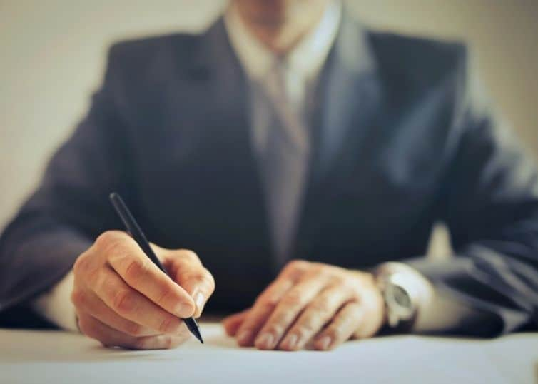 Lawyer sitting at desk filling out paperwork
