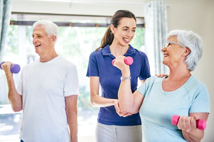Shot of an instructor assisting a senior couple with resistance training exercises in a fitness class