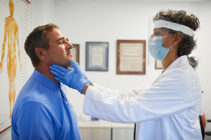 Female doctor with protective work wear assessing a patient's thyroid health