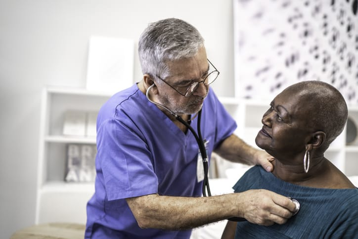 Doctor using a stethoscope to examine the heart health of an elderly African American woman