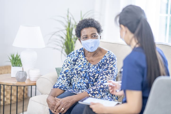 Nurse discusses COVID-19 vaccine hesitancy with patient during home visit