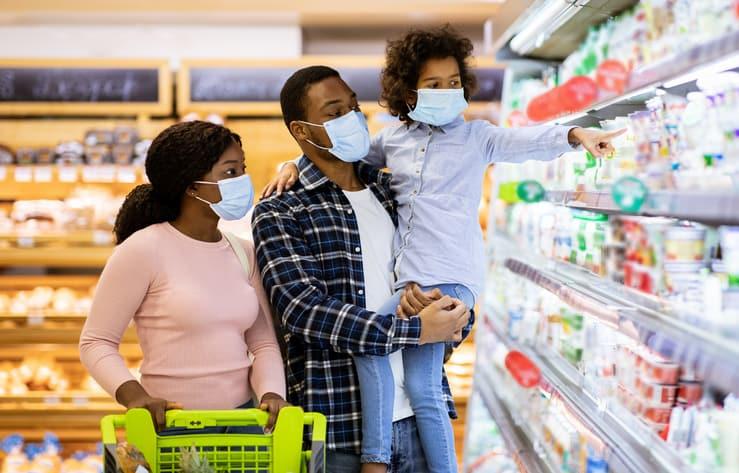 Family wearing face masks shopping at grocery store during coronavirus pandemic