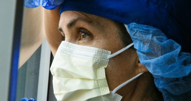 Close-up of nurse in PPE looking out hospital window, reflecting on future of nursing after pandemic