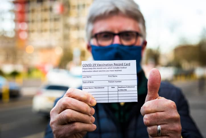 Senior man holding covid-19 vaccination record card, giving thumbs up sign