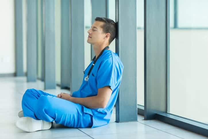 peaceful male nurse relaxing on hospital floor
