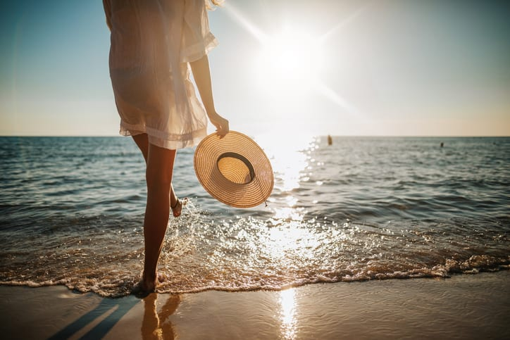 Young woman in white sun dress and walking on sandy beach at summer sunset, absorbing vitamin D