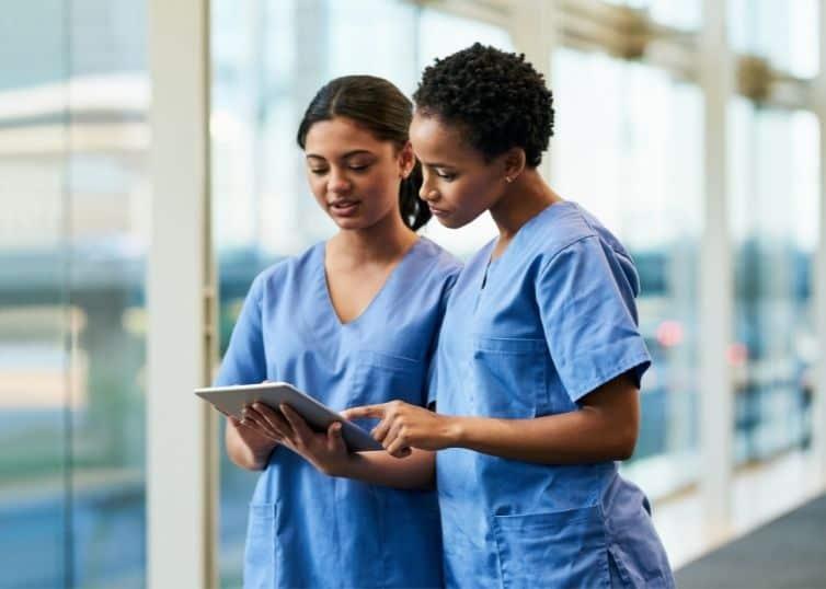 Two female nurses of color in scrubs using digital tablet at work