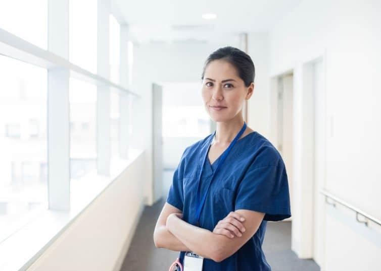 Female nurse leader in scrubs looks confidently into camera