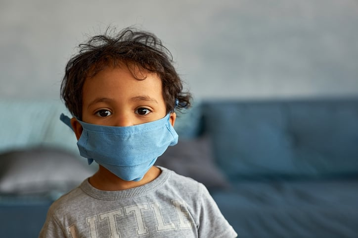 Portrait of a cute toddler boy in mask at home during COVID-19 pandemic