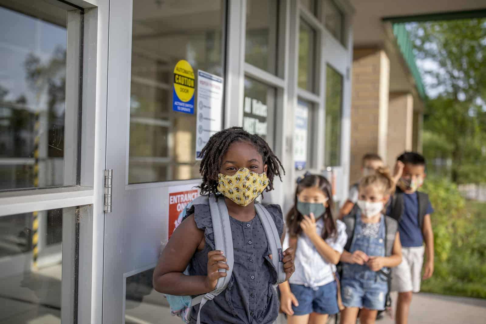 Group of kids return to school wearing face masks during the pandemic