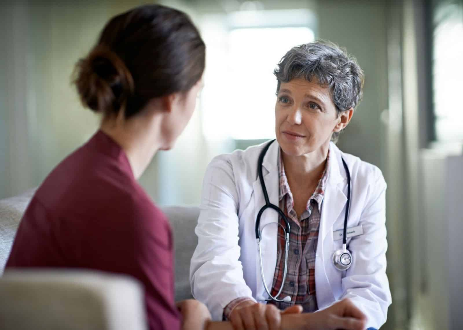 Healthcare provider speaks compassionately with young female patient showing possible signs of domestic violence