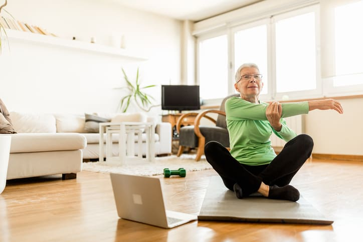Senior woman exercising at home using an online trainer service