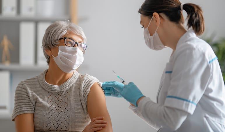 Doctor giving a senior woman a third vaccine dose.