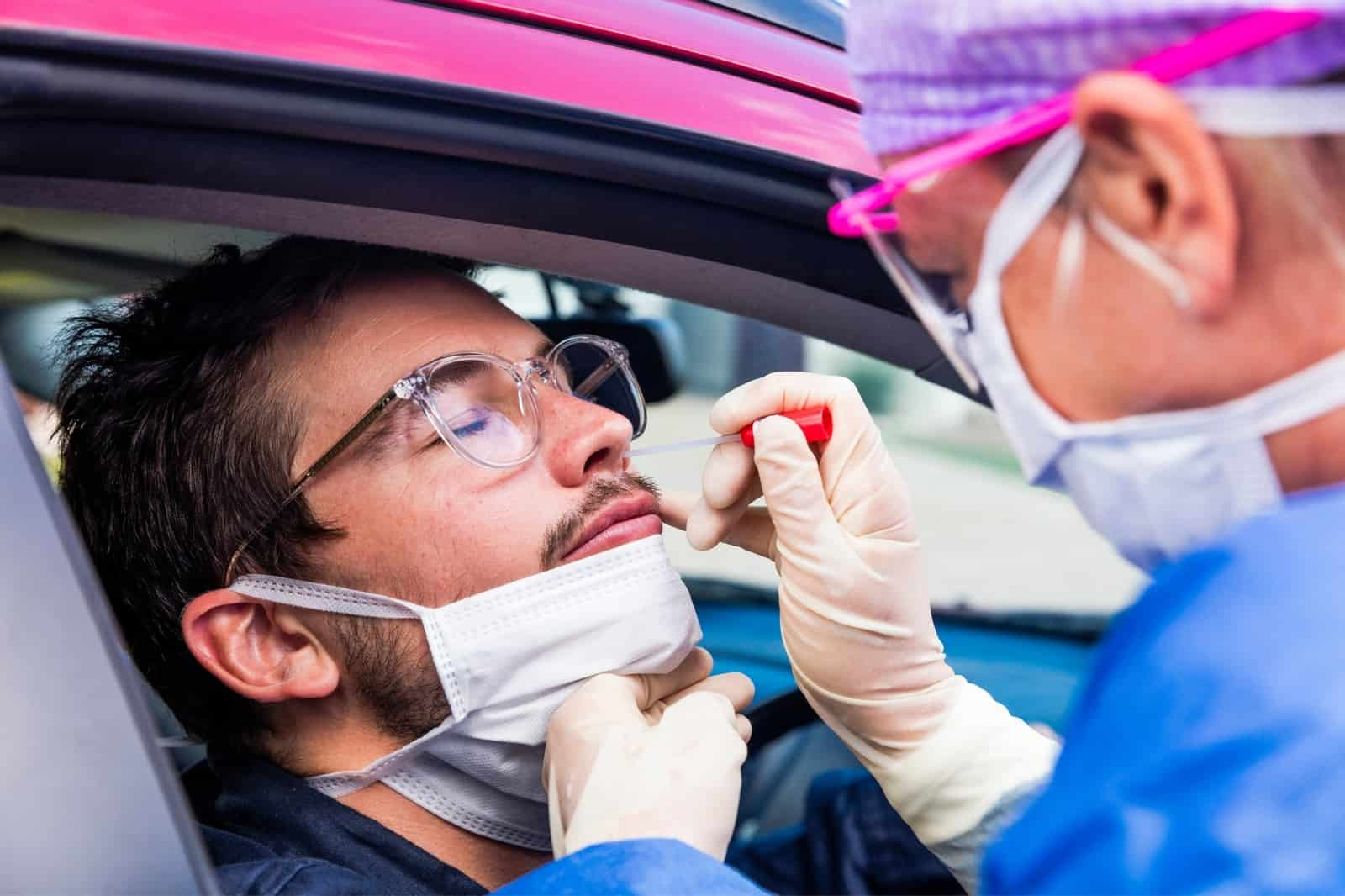 Health professional wearing PPE tests man for new COVID-19 variant at drive-up testing site