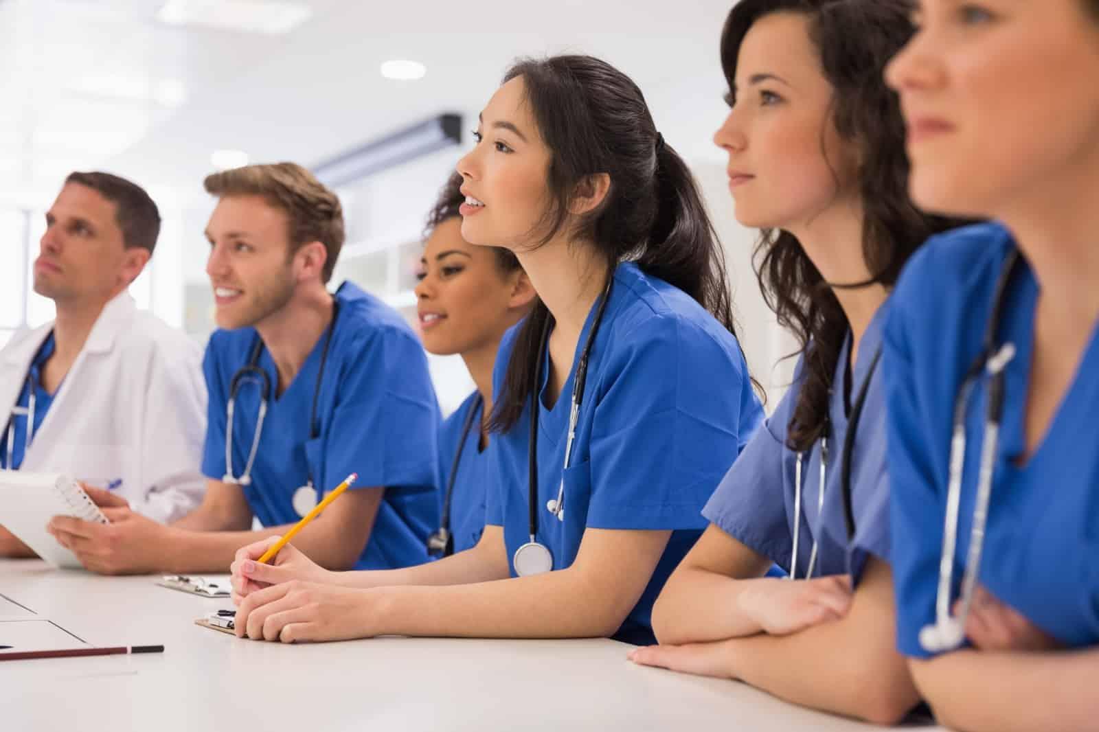 Nursing students in scrubs attend class at nursing school