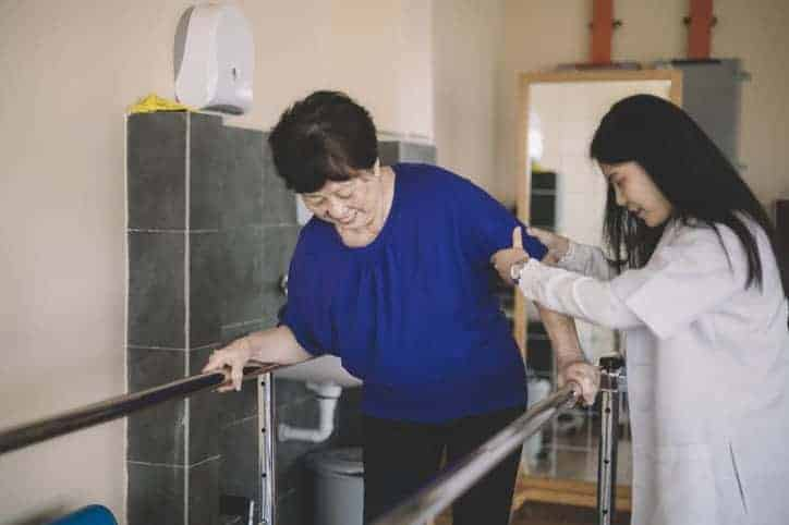 Caring asain female physical therapist helps senior woman stroke victim with body neglect in rehab center