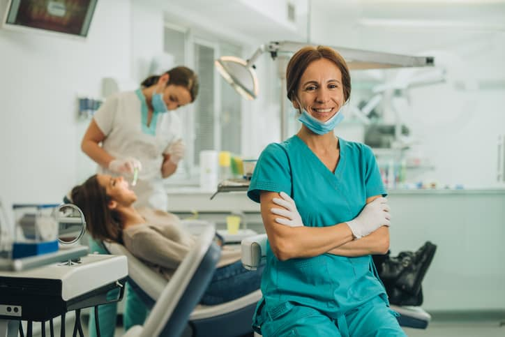 Smiling dentist sitting at dentist's office with her arms crossed and looking at camera, with a staff member treating a patient in the background.