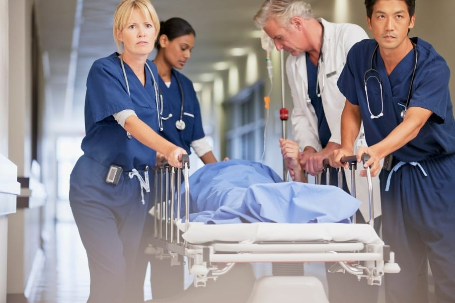 Emergency nurses and doctor quickly wheel patient bed down hospital hallway