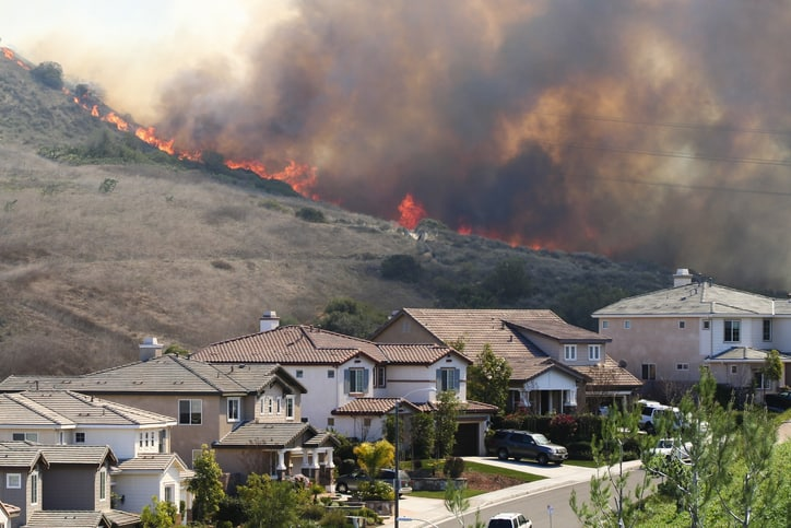 A recent southern california wildfire burning extremely close to homes.