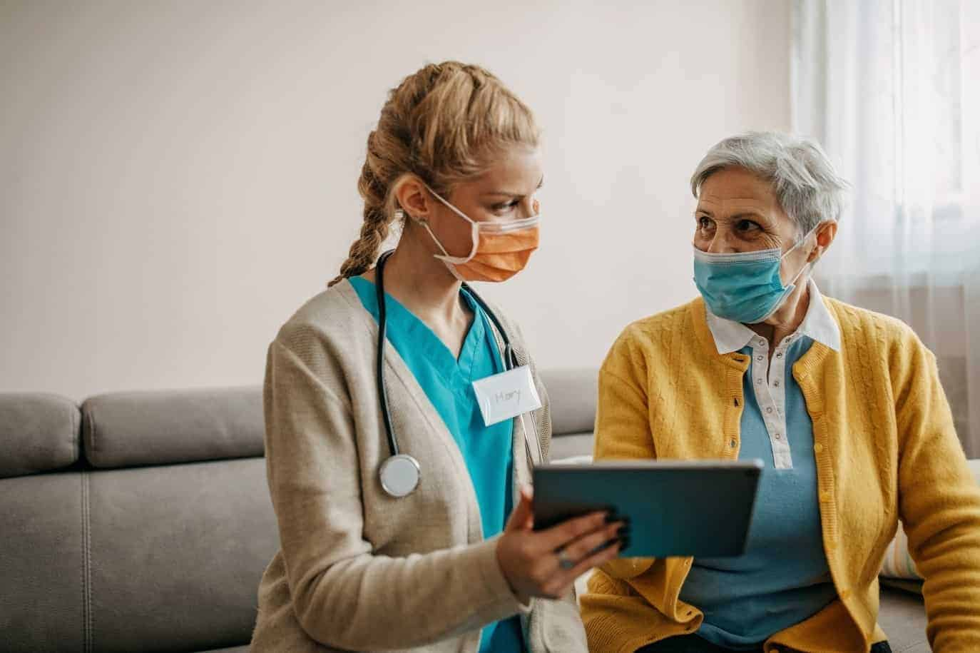 Healthcare professional reviews fitness plan with senior patient during COVID-19 pandemic, Healthy Aging Month concept