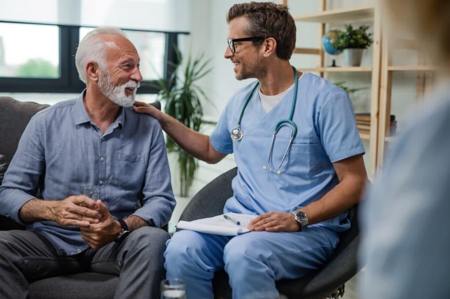 Male nurse comforts chronic pain patient, provides pain relief to mature male patient