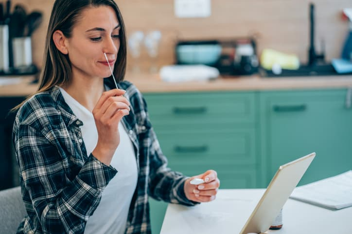 Woman holding self-testing swab, taking rapid COVID-19 home test