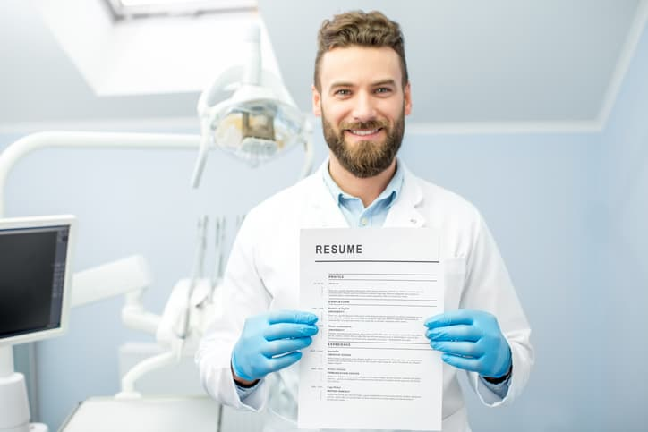 Professional male dentist holding dental resume for a new job standing at the dental office