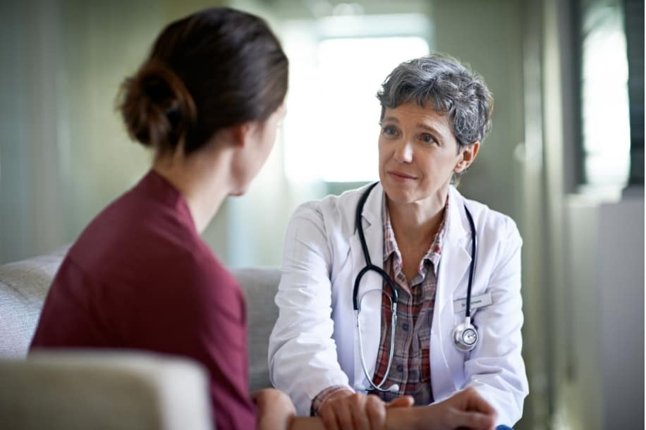 Healthcare professional shows compassion while speaking with a young woman about domestic violence