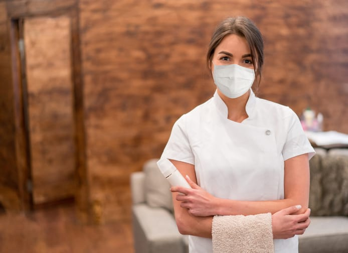 Massage therapist working at a spa and wearing a face mask during the COVID-19 pandemic