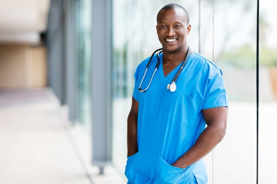African American male nurse smiling, standing in hospital hallway