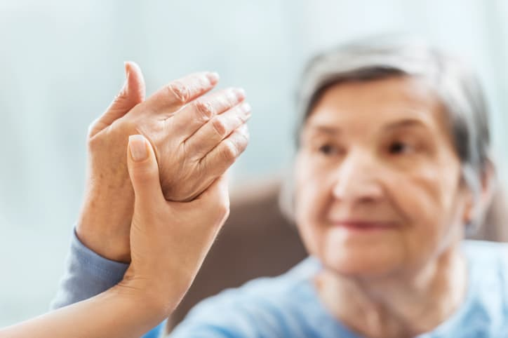 A senior woman receiving physical therapy, sensory reeducation exercises for the hand