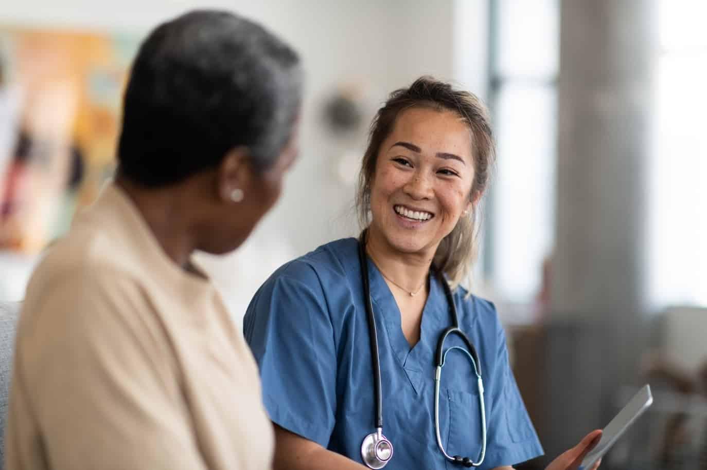 Smiling nurse talks with breast cancer patient, reviews survivorsip care plan